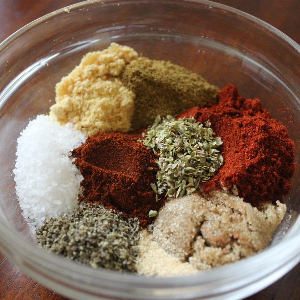 a colorful assortment of ground spices and dried herbs in a glass bowl before they've been mixed together
