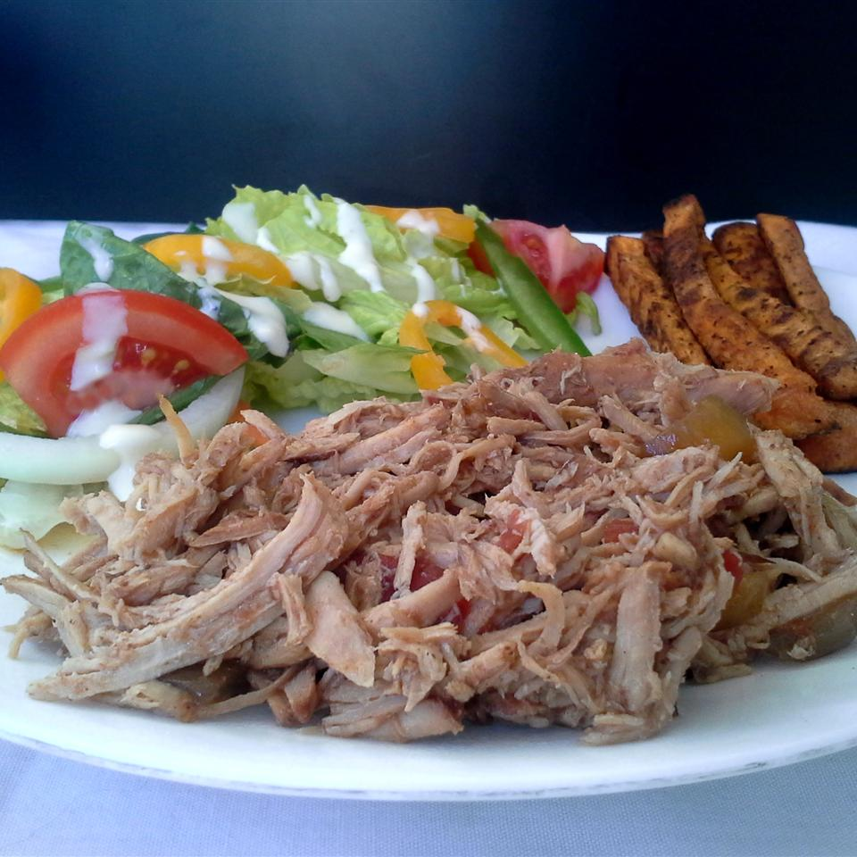 shredded pork on a white plate with salad in the background