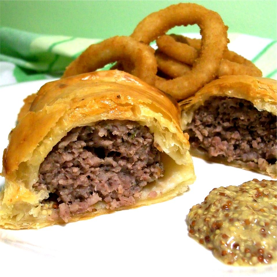 a sausage roll cut in half to show the filling, on a white plate with mustard for dipping