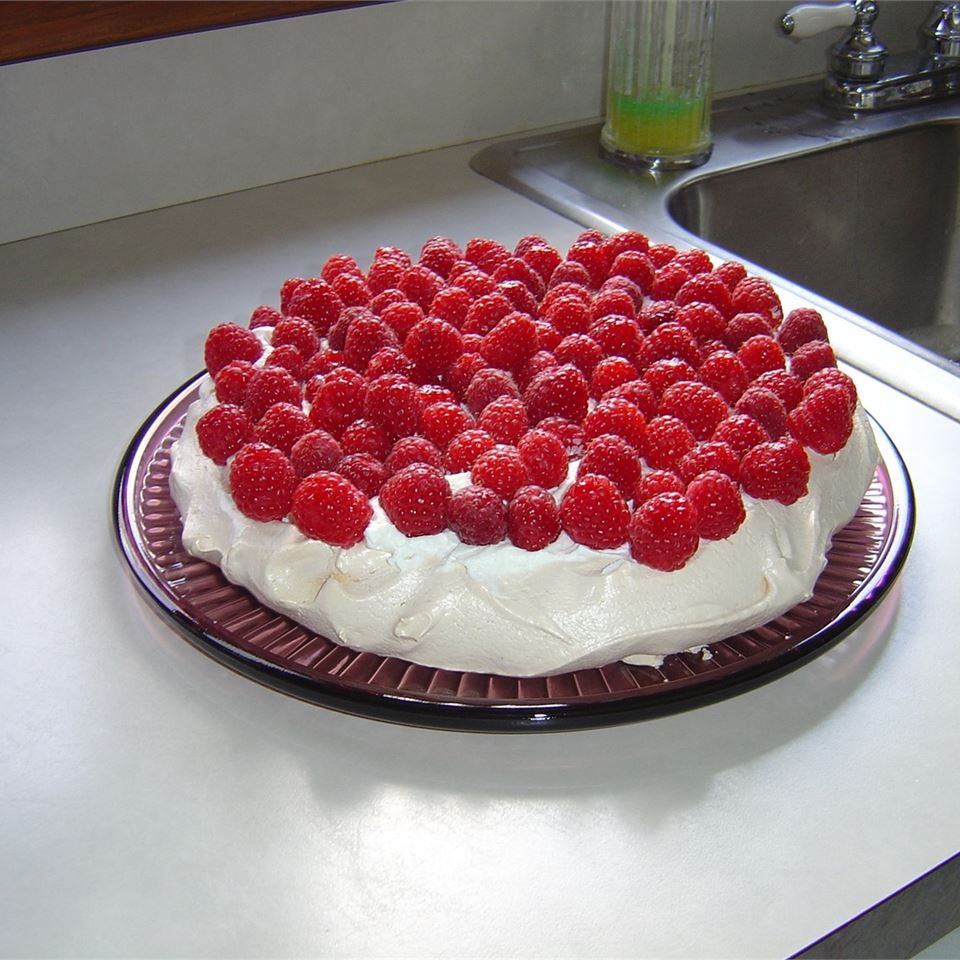 a baked meringue shell topped with fresh raspberries