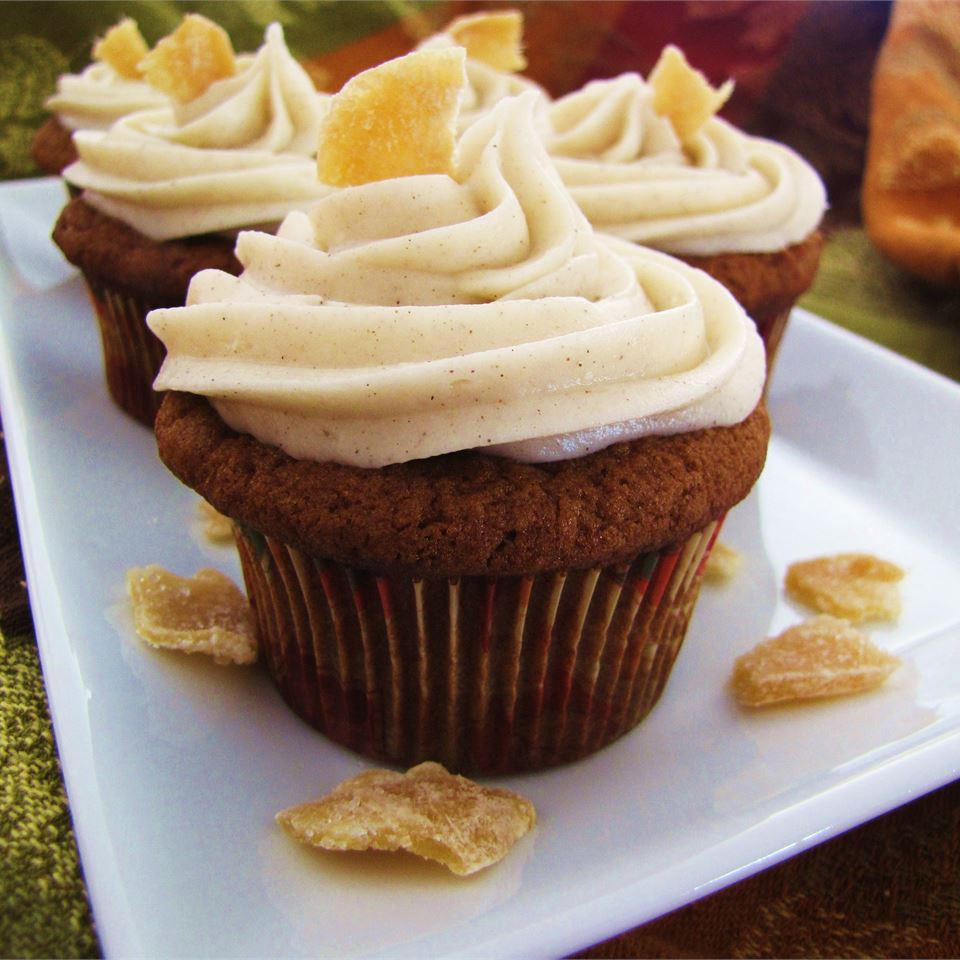 closeup of cupcakes with piped cream cheese frosting and candied ginger garnish