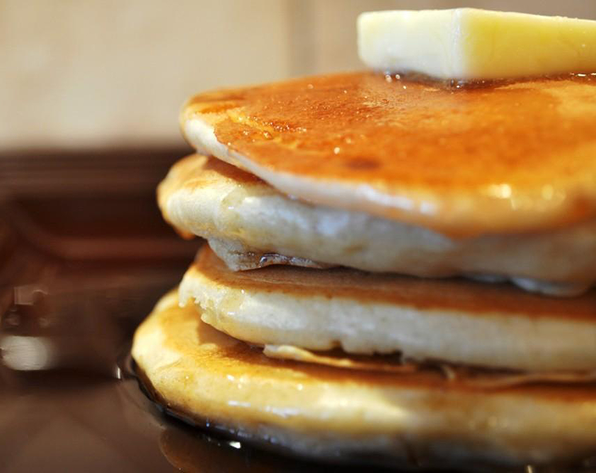 closeup view of a stack of four pancakes with a pat of butter on top and maple syrup poured over the sides