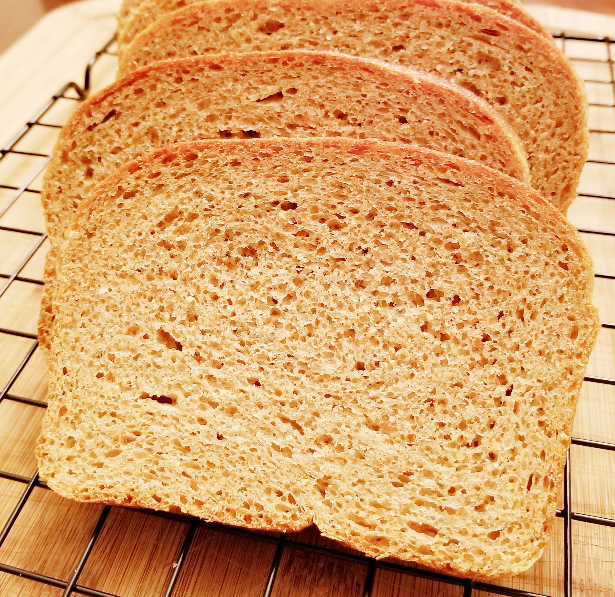 closeup of sliced wheat bread on a cooling rack