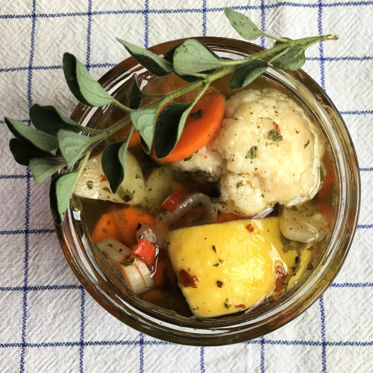 top-down view of a jar of vegetables ready for pickling: cauliflower, carrot slices, yellow squash, and fresh herbs