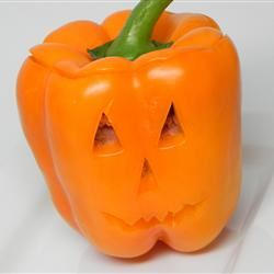 an orange bell pepper cut like a Halloween jack-o-lantern with triangle eyes and nose and a jagged smile