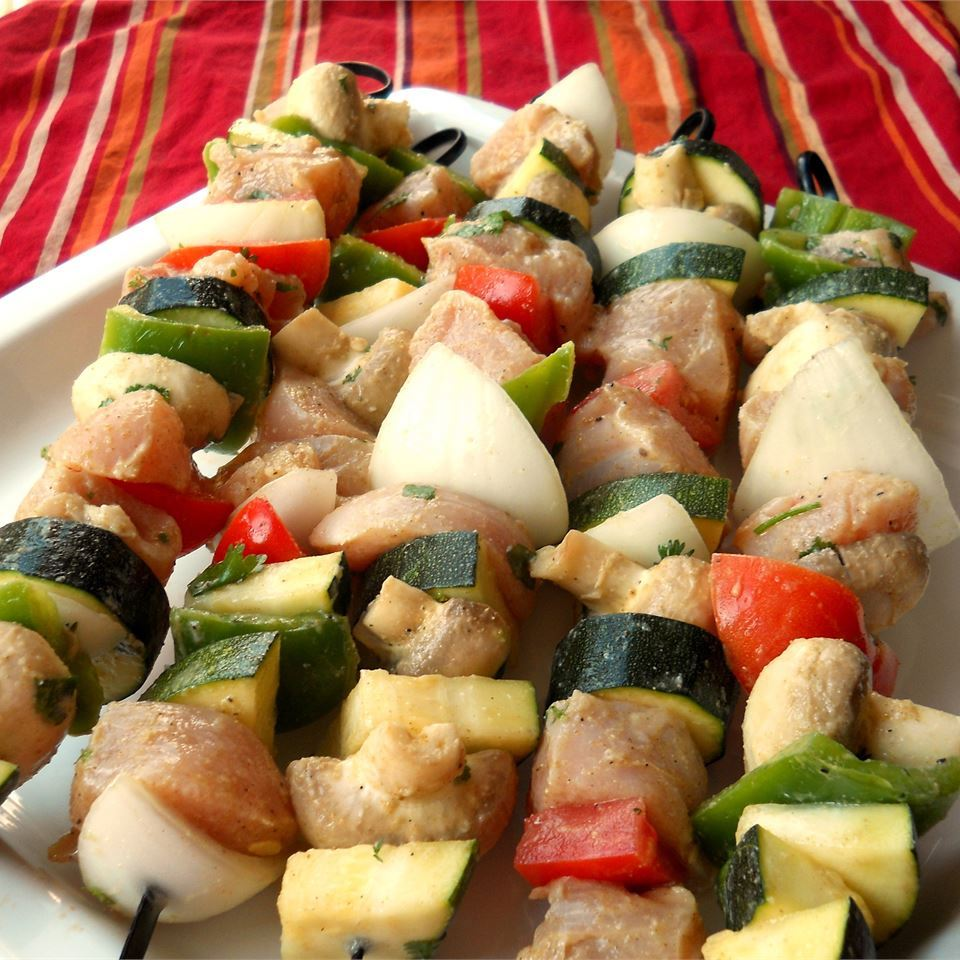 Chicken Kabobs Mexicana on a white plate with a red table cloth