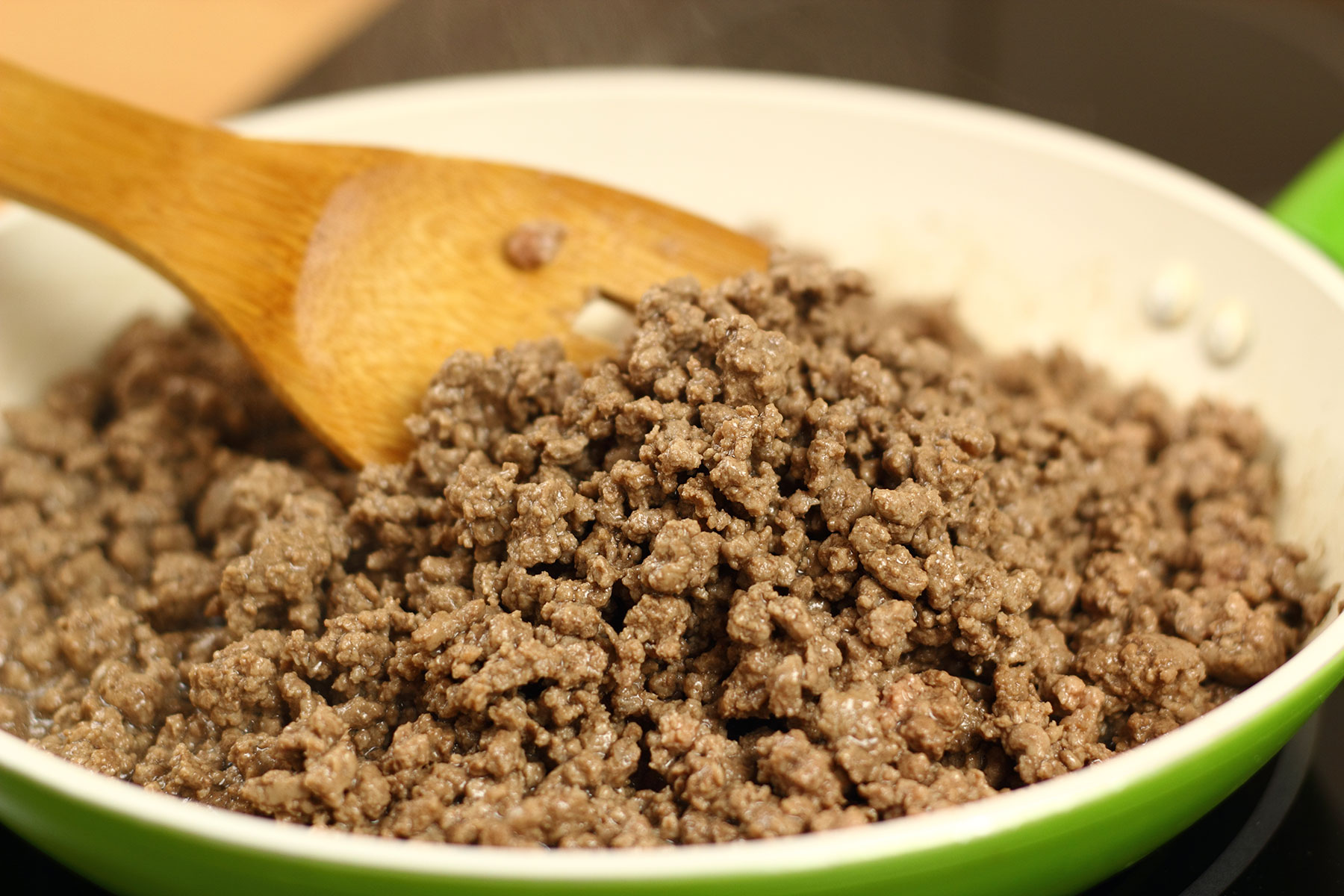 Browning ground beef in skillet with wooden spoon