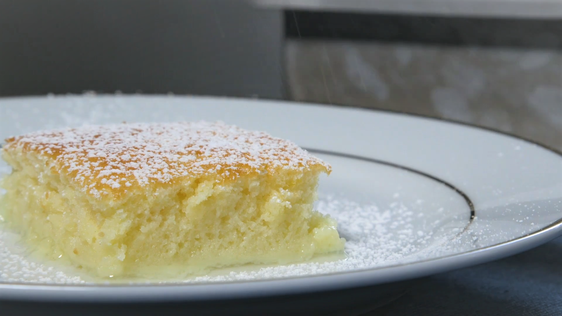 Slice of lemon pudding cake dusted with confectioners' sugar