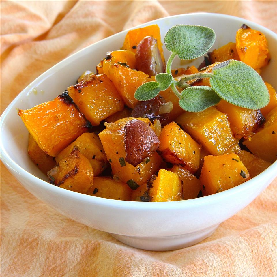 butternut squash with grapes and sage in a white dish