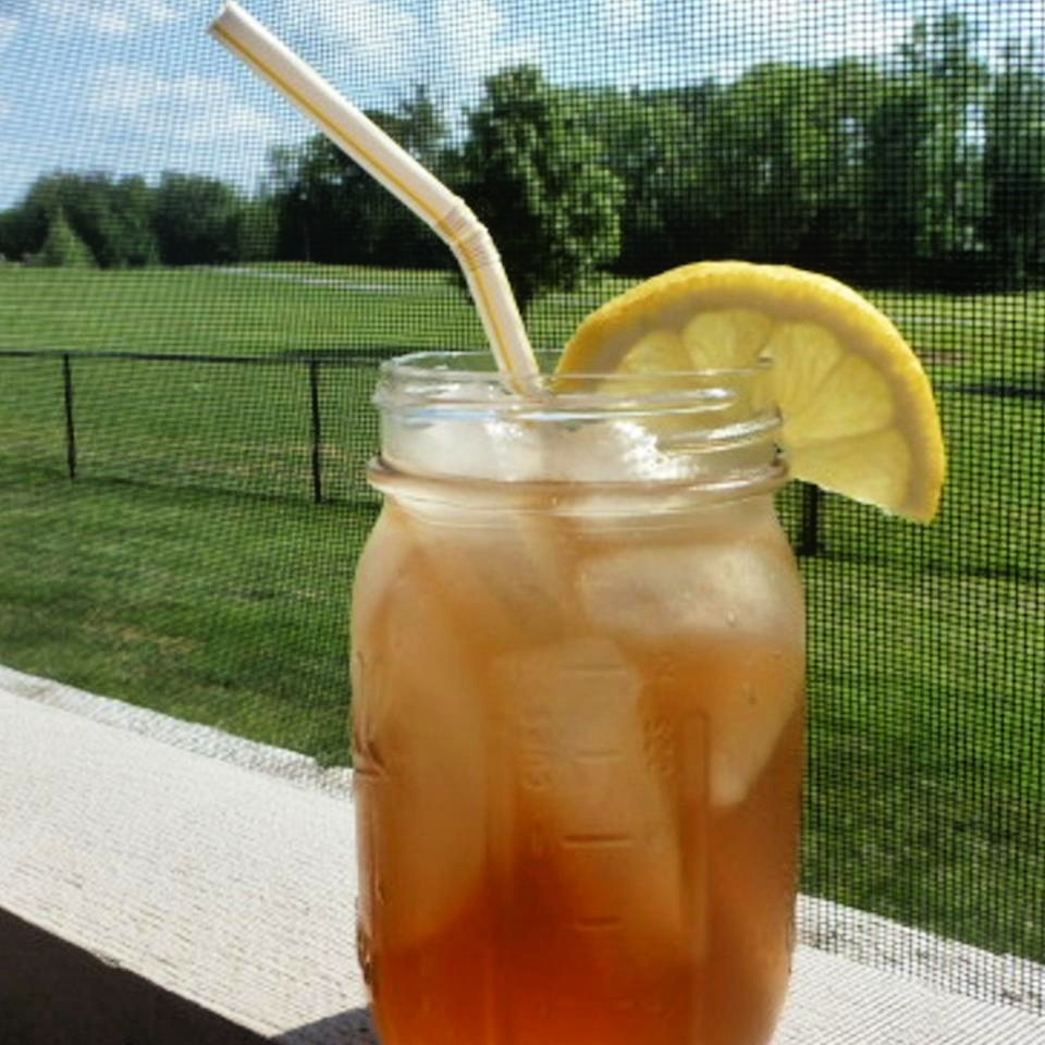 long island ice tea on the rocks in a jar with lemon garnish and a straw