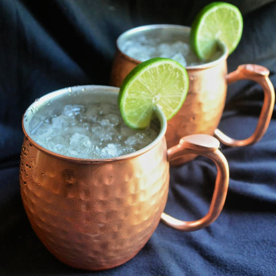 moscow mule cocktails in hammered copper mugs and lime garnish