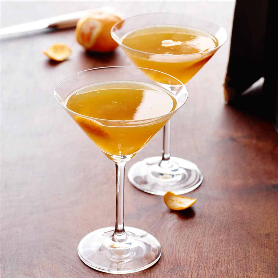 two citrus and whiskey cocktails in martini glasses