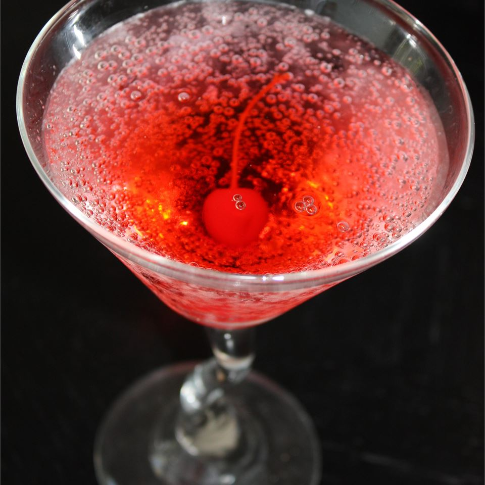 shirley temple mocktail in a champagne glass with cherry garnish