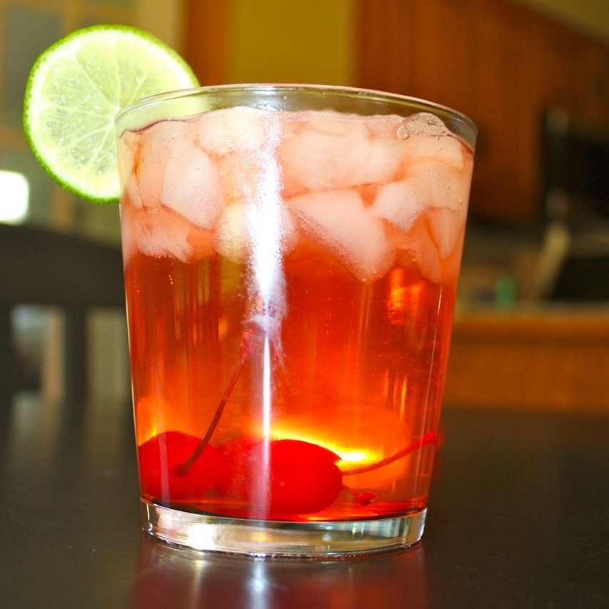 cherry bomb cocktail on the rocks with cherry and lime garnish