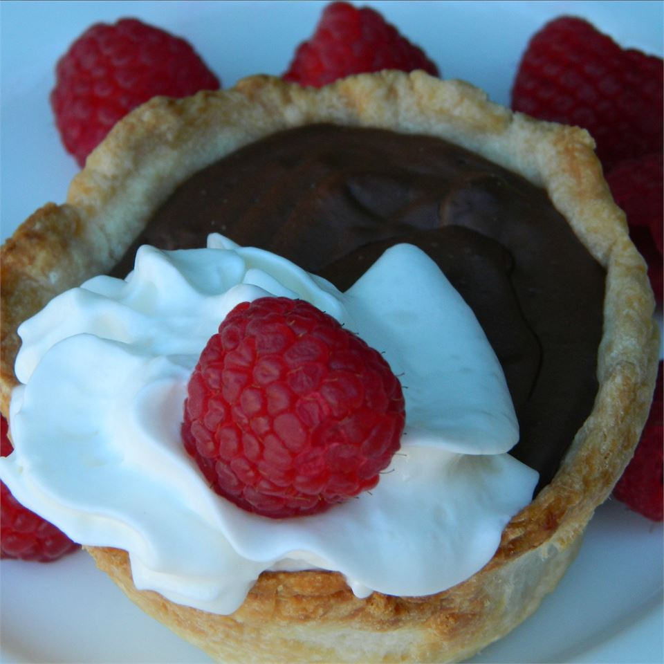 Pam's Sugar Free Chocolate Pie topped with whipped cream and berries on a white background