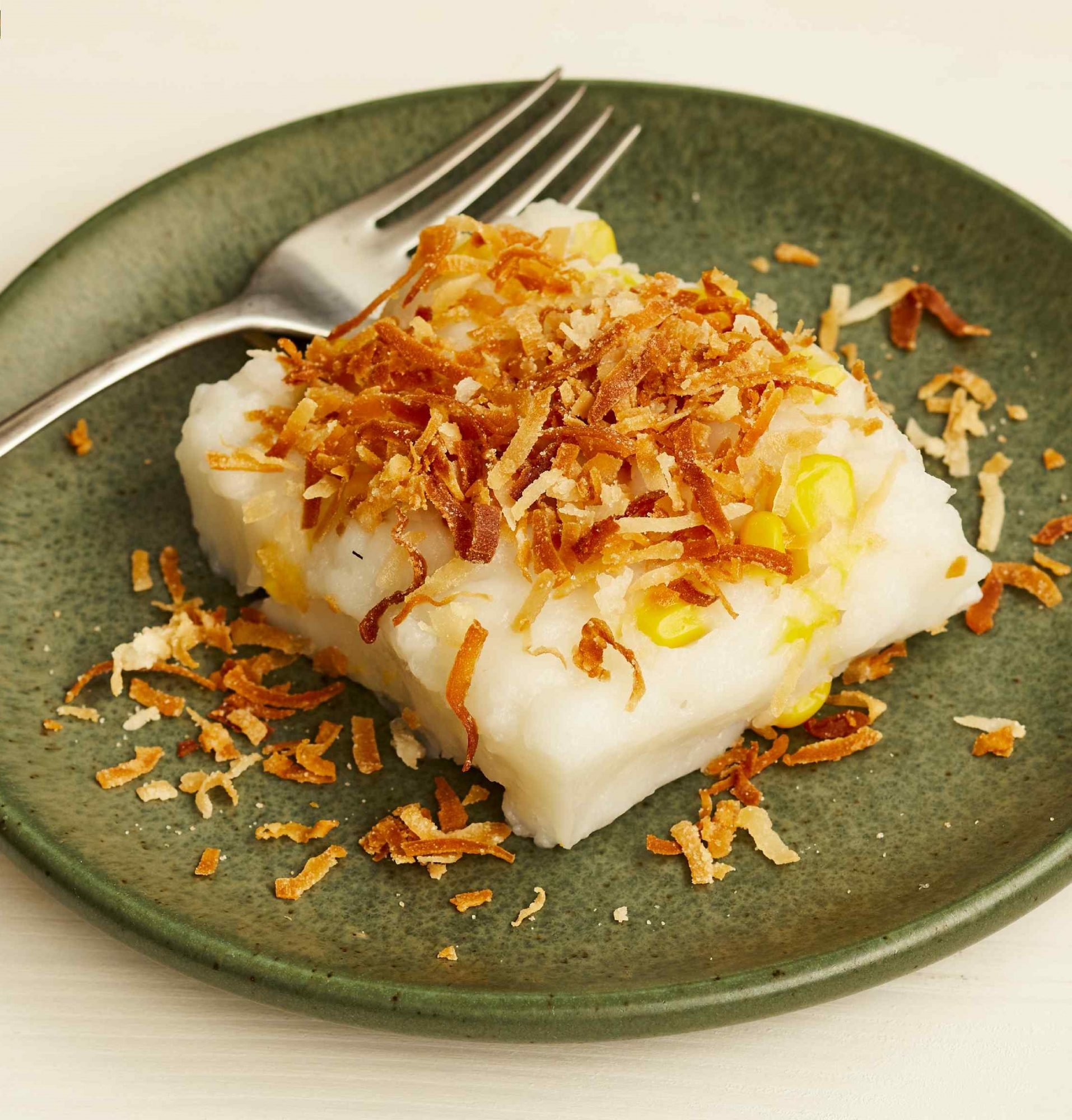 Maja Blanca Coconut Pudding topped with toasted coconut on a green plate