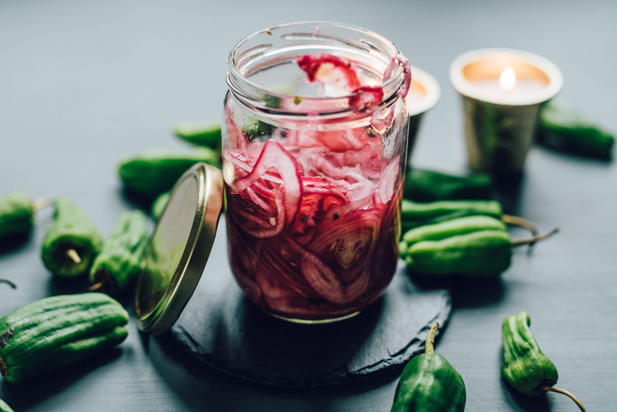 Jar of pickled red onions surrounded by peppers