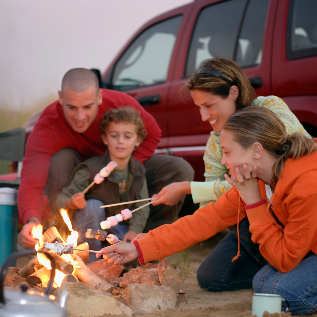 family roasting marshmallows while car camping