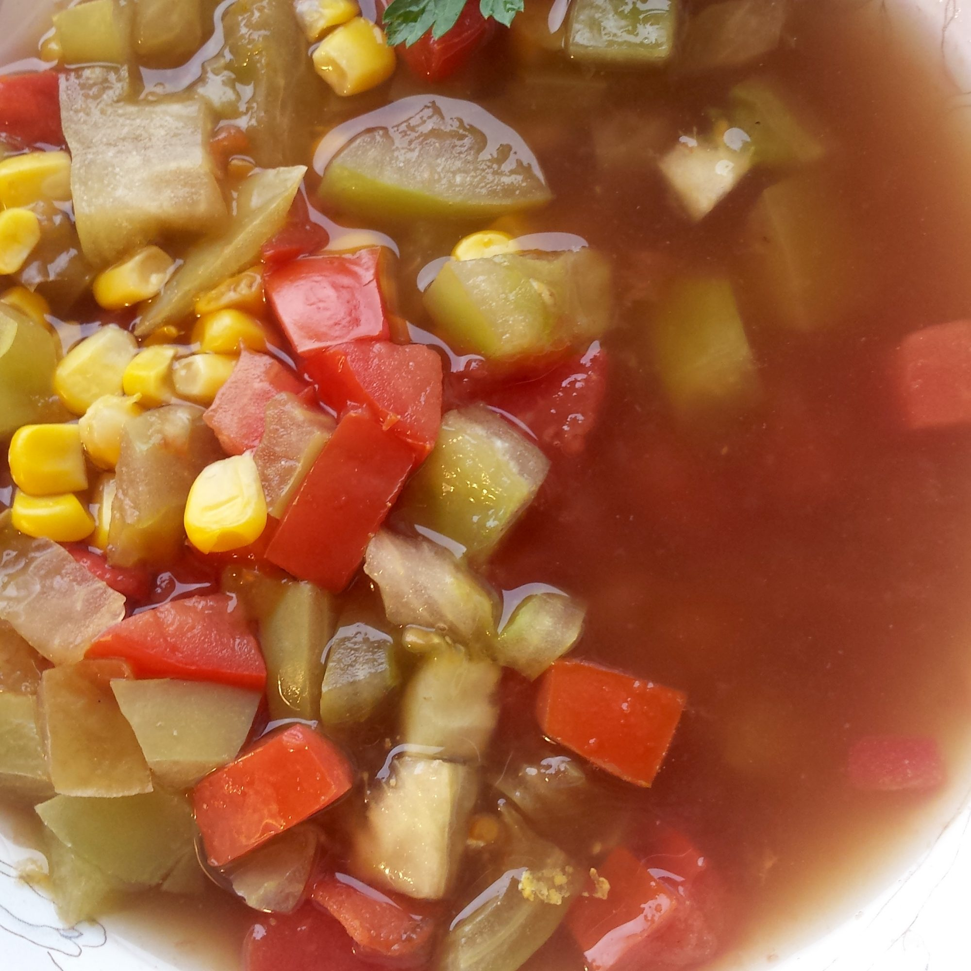 Green and Red Tomato and Corn Soup in a white bowl
