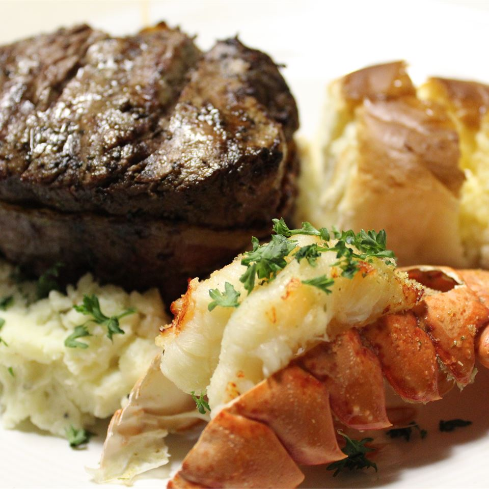 lobster tail served with steak and potatoes - your classic surf and turf dinner