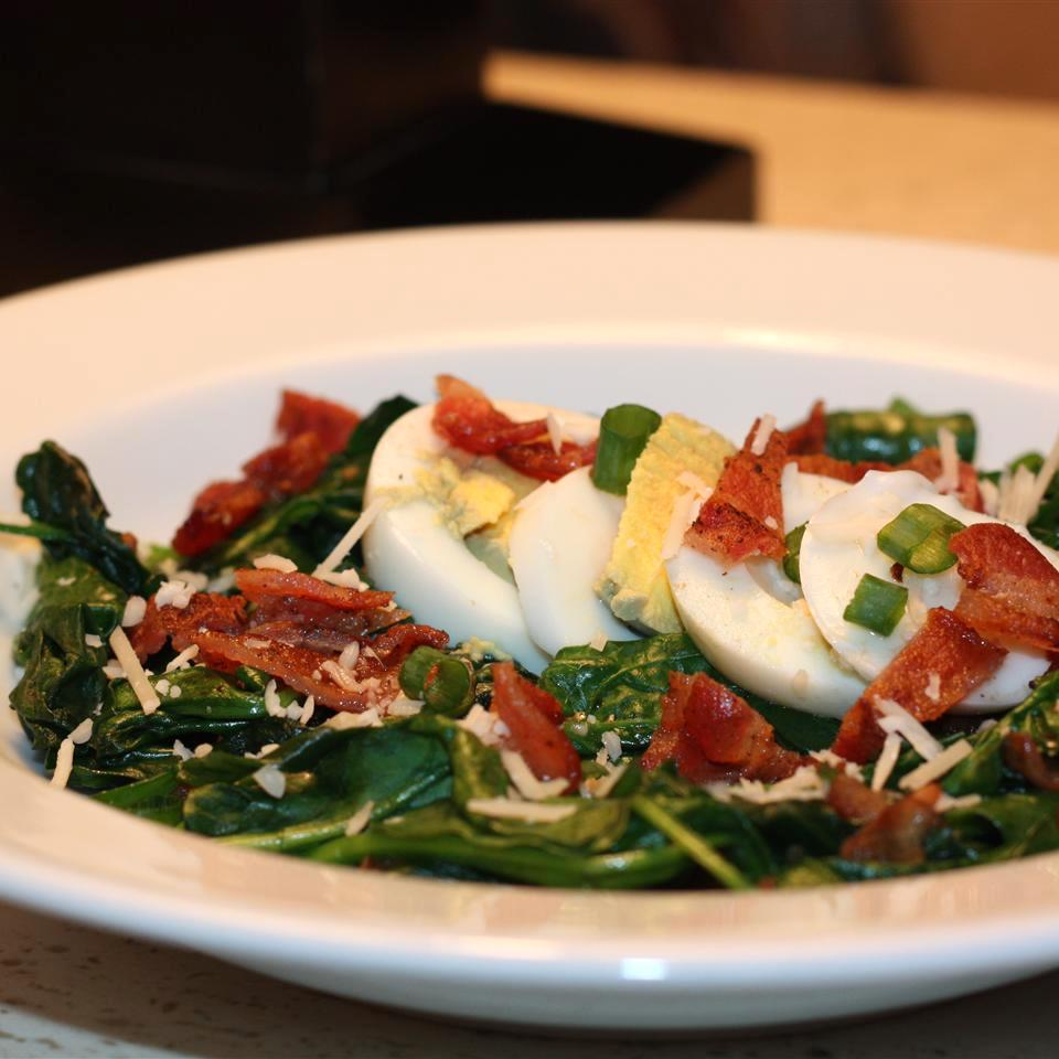 cooked spinach with boiled eggs and bacon on top in a white bowl