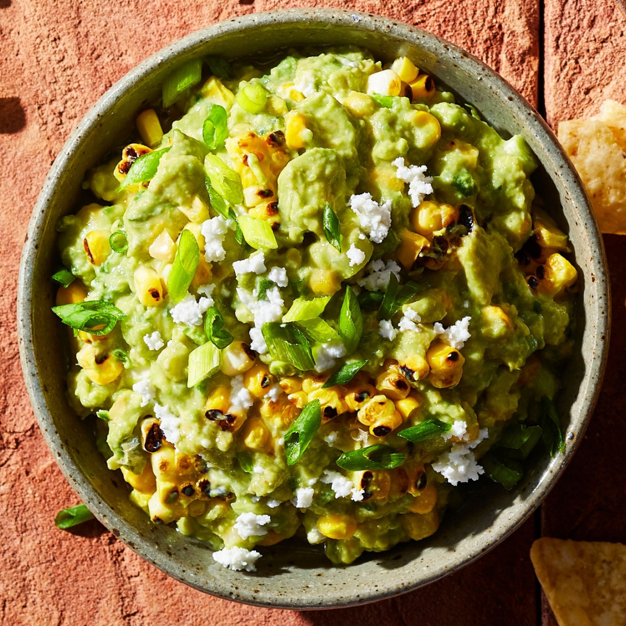 guacamole with roasted corn, green onion, goat cheese, and serrano pepper in a bowl