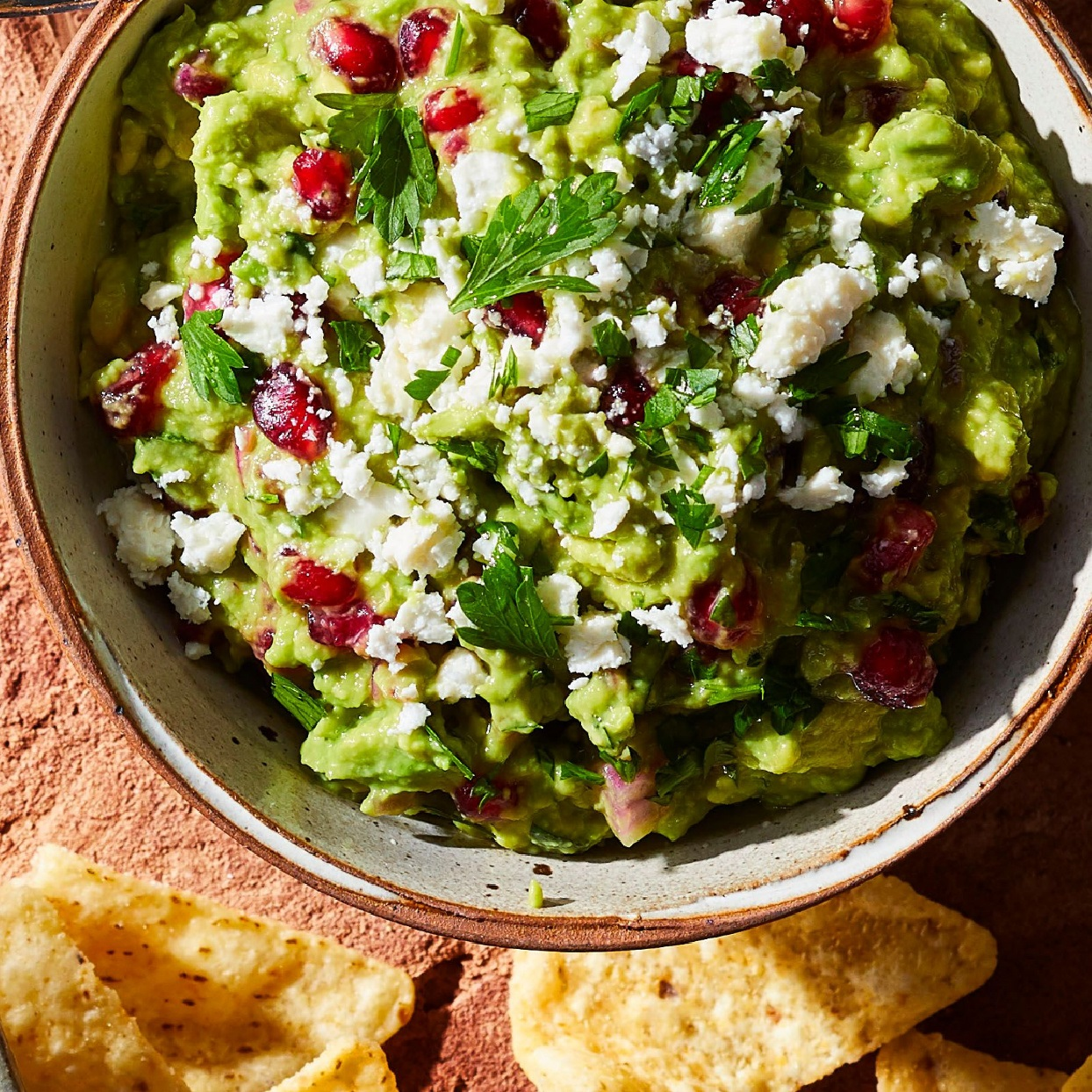 guacamole with pomegranate seeds, parsley, feta cheese, and red onion in a bowl with tortilla chips