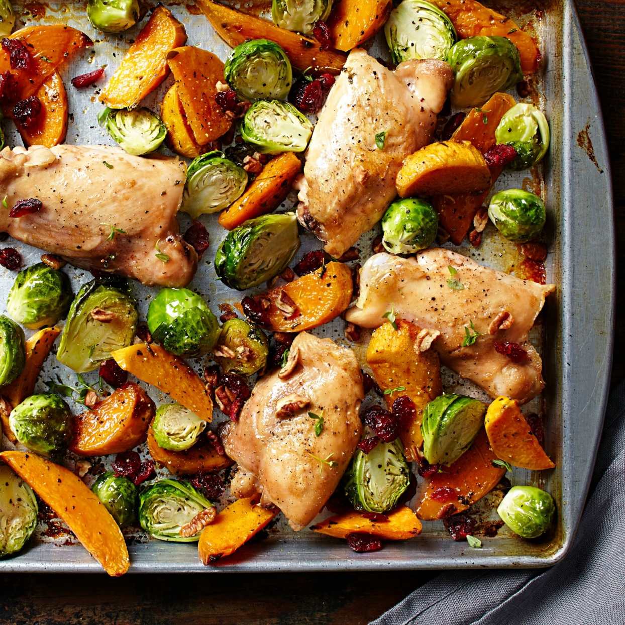 chicken thighs, brussels sprouts, and sweet potatoes roasted on a sheet pan