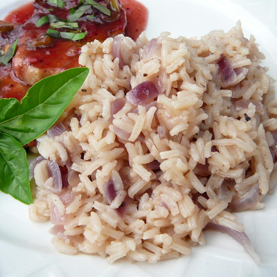 Onion Rice on a white plate with herbs