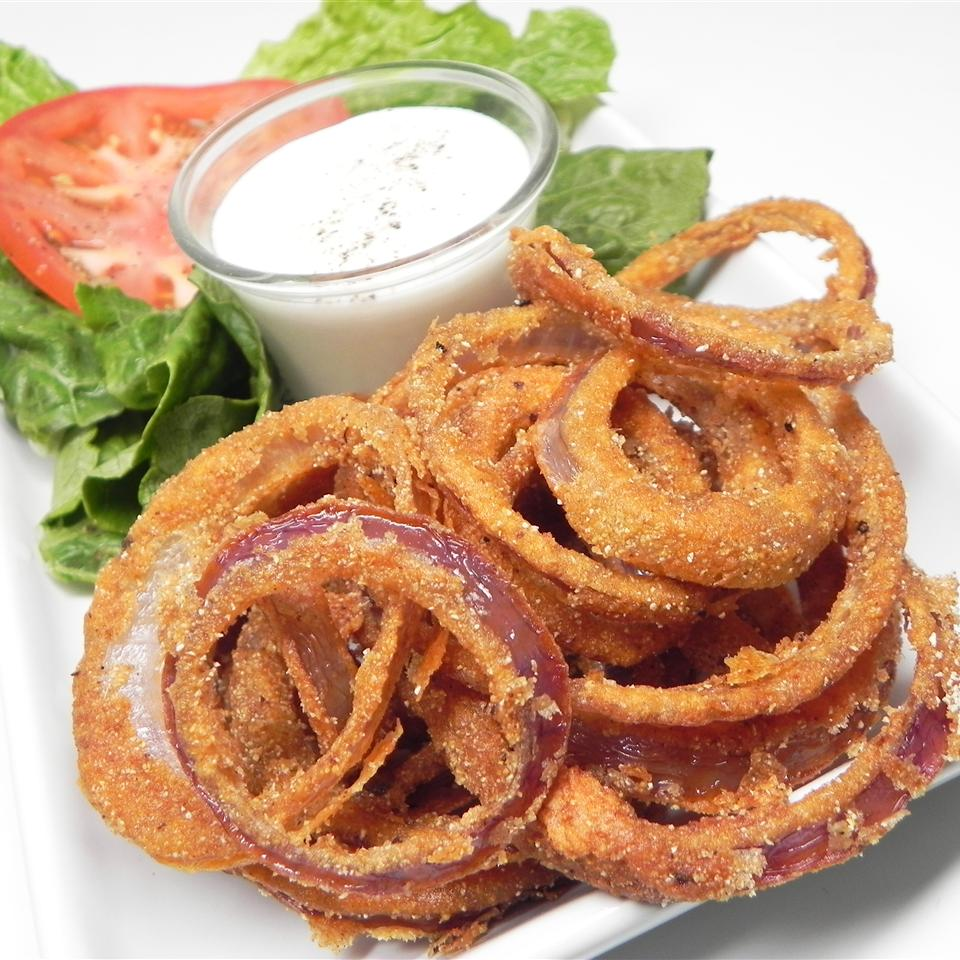 Onions rings on a white plate with a side of ranch