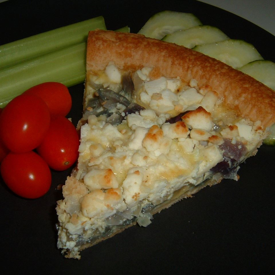 Red Onion and Goat Cheese Tart on a plate with vegetables