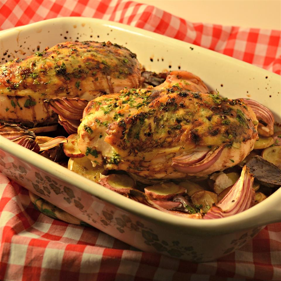 Balsamic Chicken with Red Onions and Potatoes in a white casserole dish on red checkered picnic cloth
