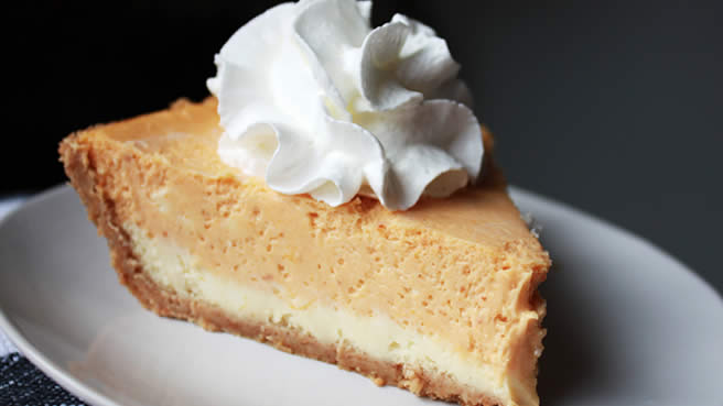 closeup of a slice of cheesecake with a white cream cheese layer on the bottom and a pumpkin layer on top, garnished with a rosette of whipped cream