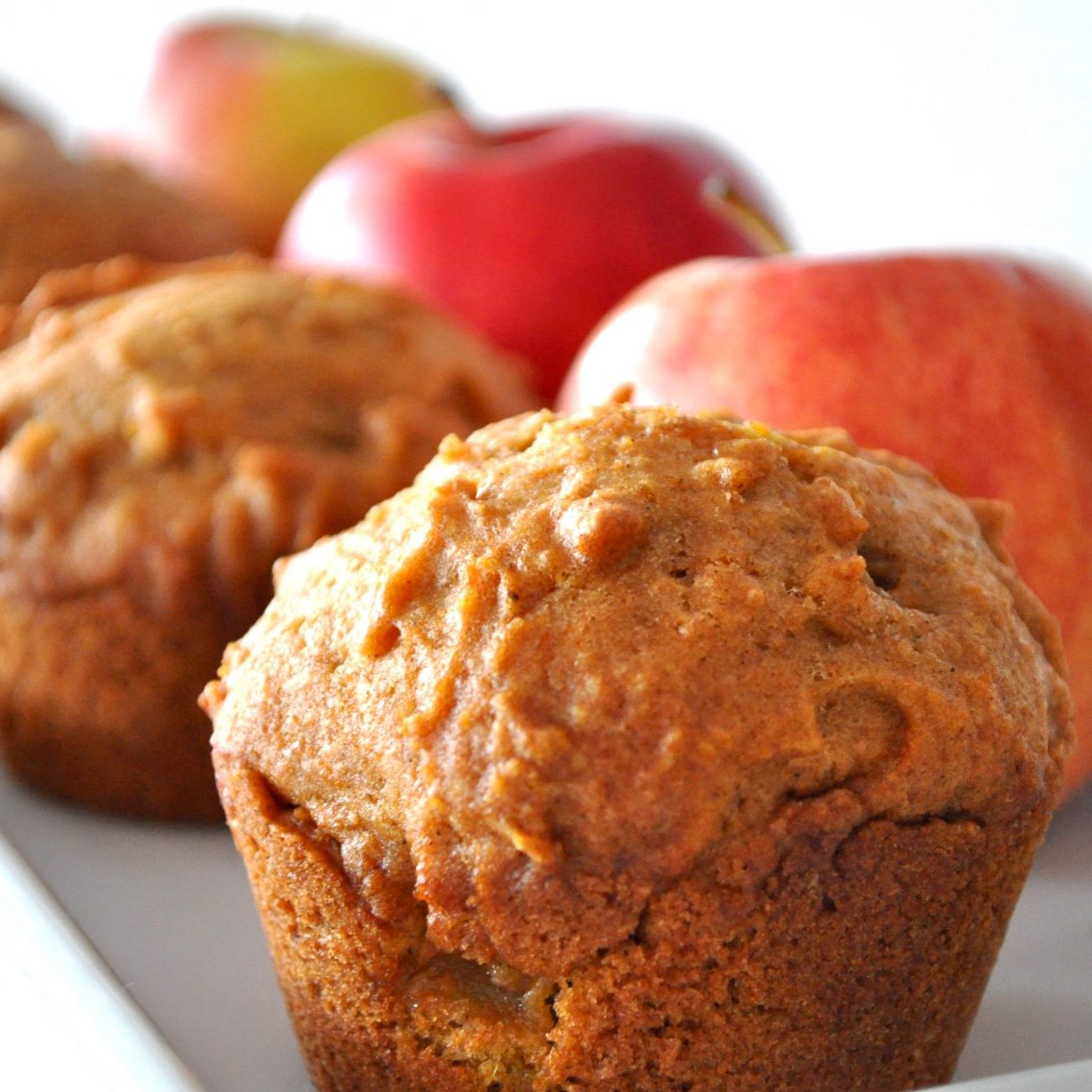 Pumpkin Apple Streusel Muffins on a white dish in front of red apples