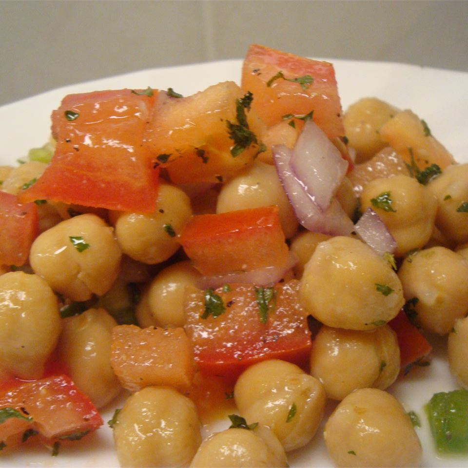 Chickpea Salad with Red Onion and Tomato on a white plate