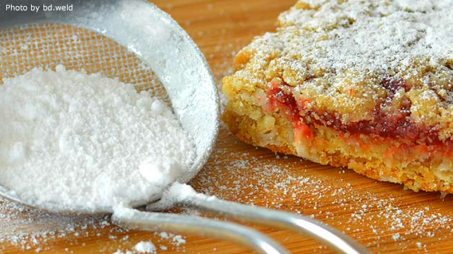 closeup of a mesh sieve of powdered sugar on a cutting board next to a fruit-filled bar