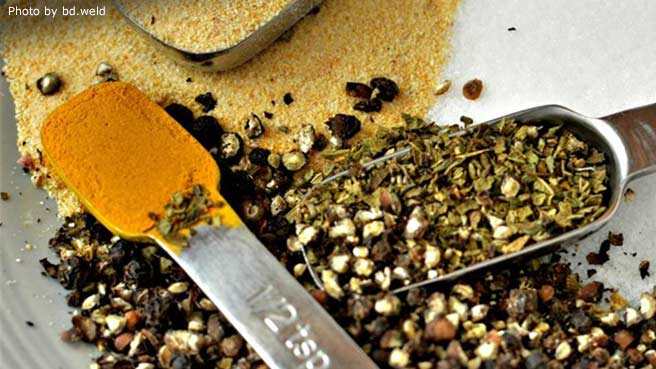 measuring spoons and mixed spices: garlic powder, turmeric, and cracked black pepper