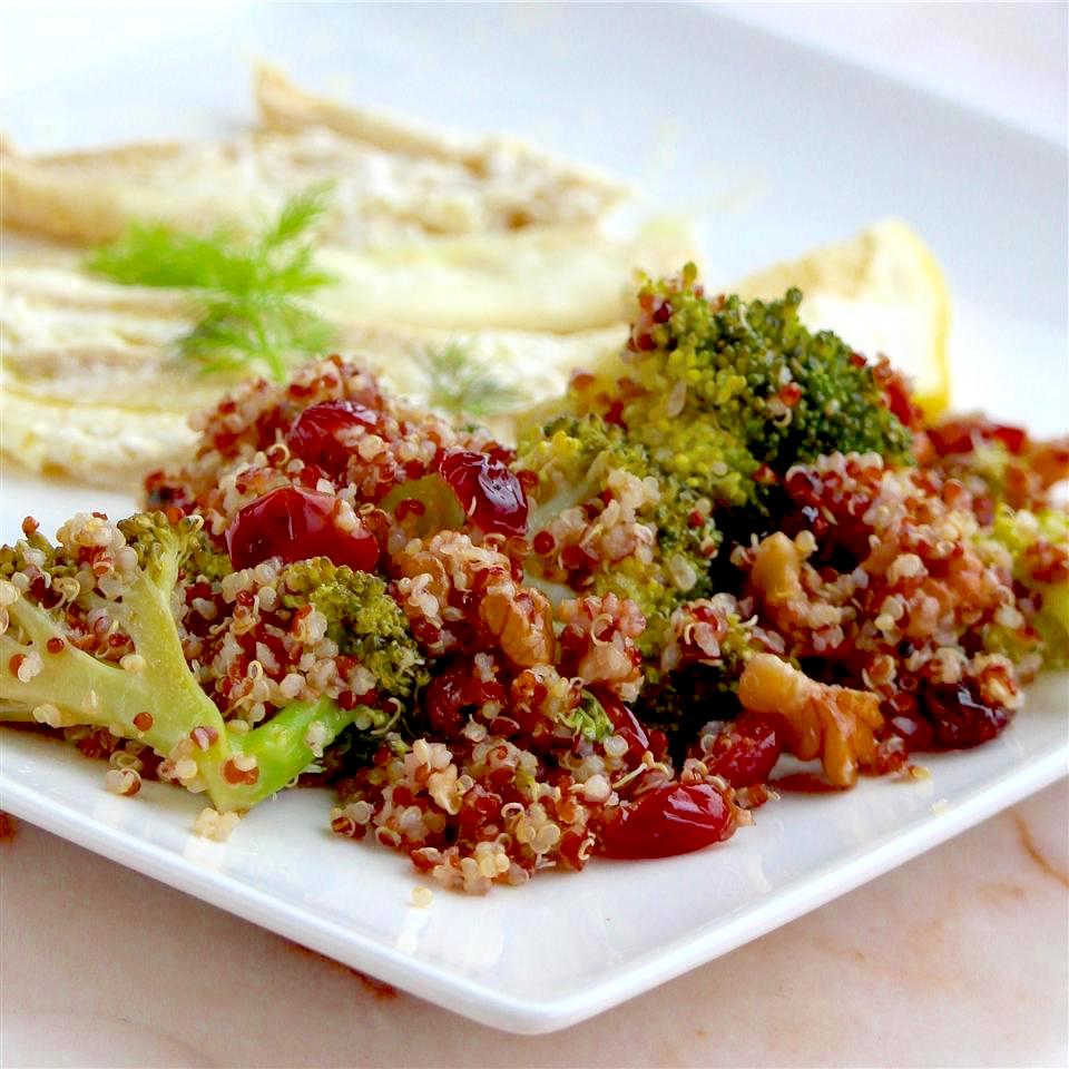 Cranberry Quinoa Salad with Broccoli on a white plate served with hummus
