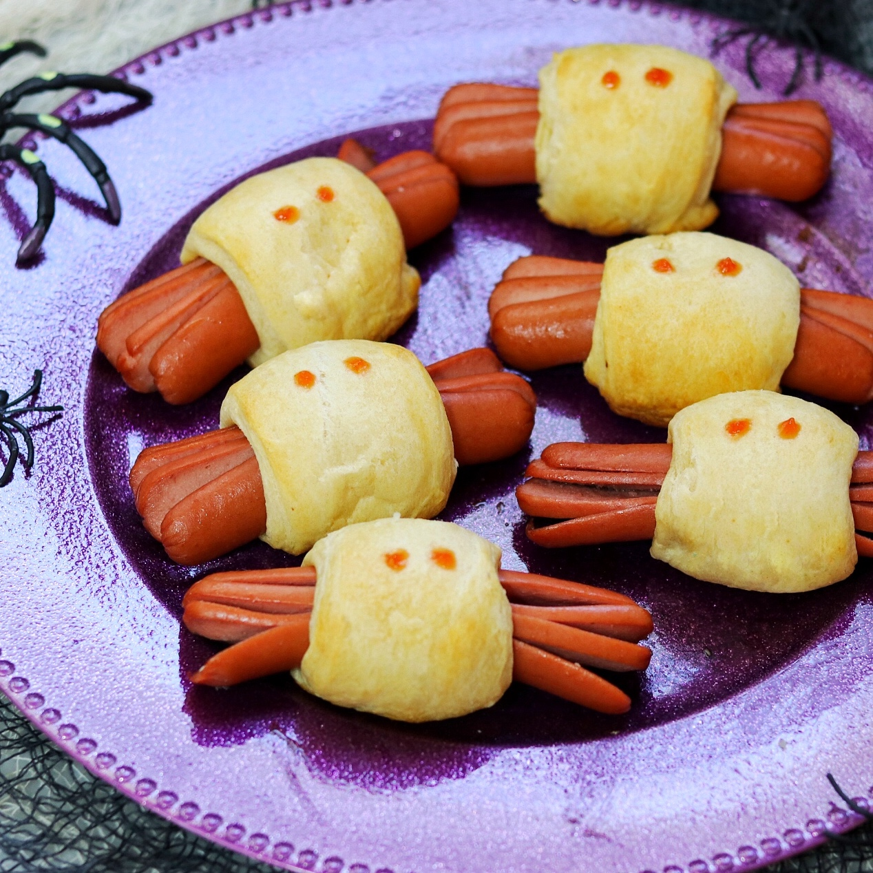 Spooky Spider Halloween Hot Dogs on a purple plate with plastic spider decorations