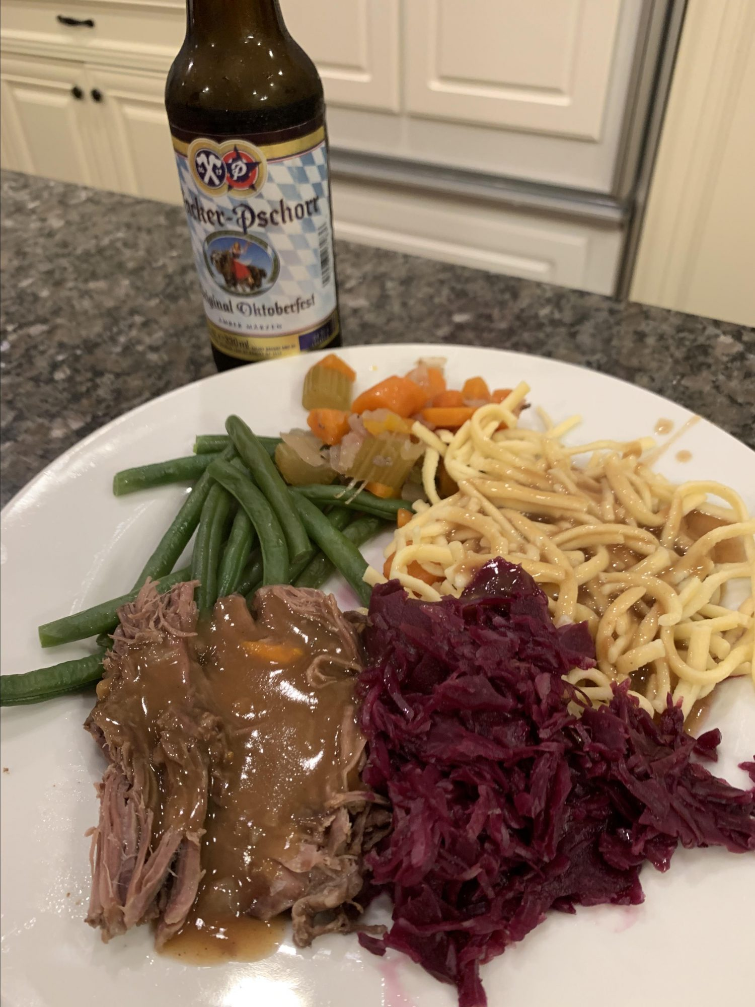 A German dinner with braised beef chuck, red cabbage, and egg noodles, accompanied by a bottle of Hacker-Pschorr beer