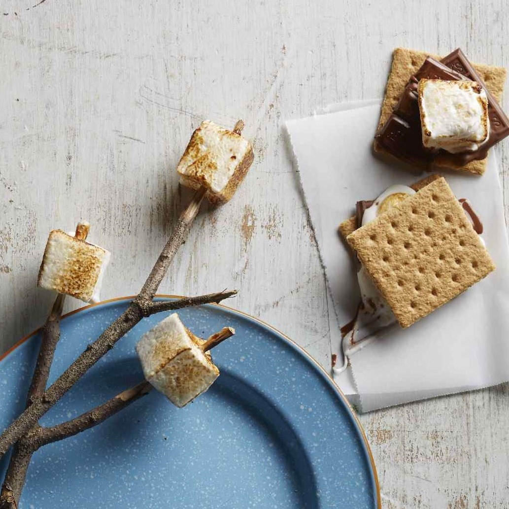 toasted marshmallows on a stick with graham crackers and chocolate for s'mores