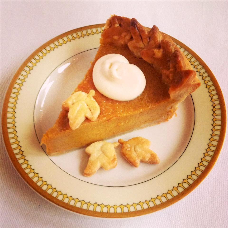 Chef John's Pumpkin Pie topped with whipped cream and pie crust leaves