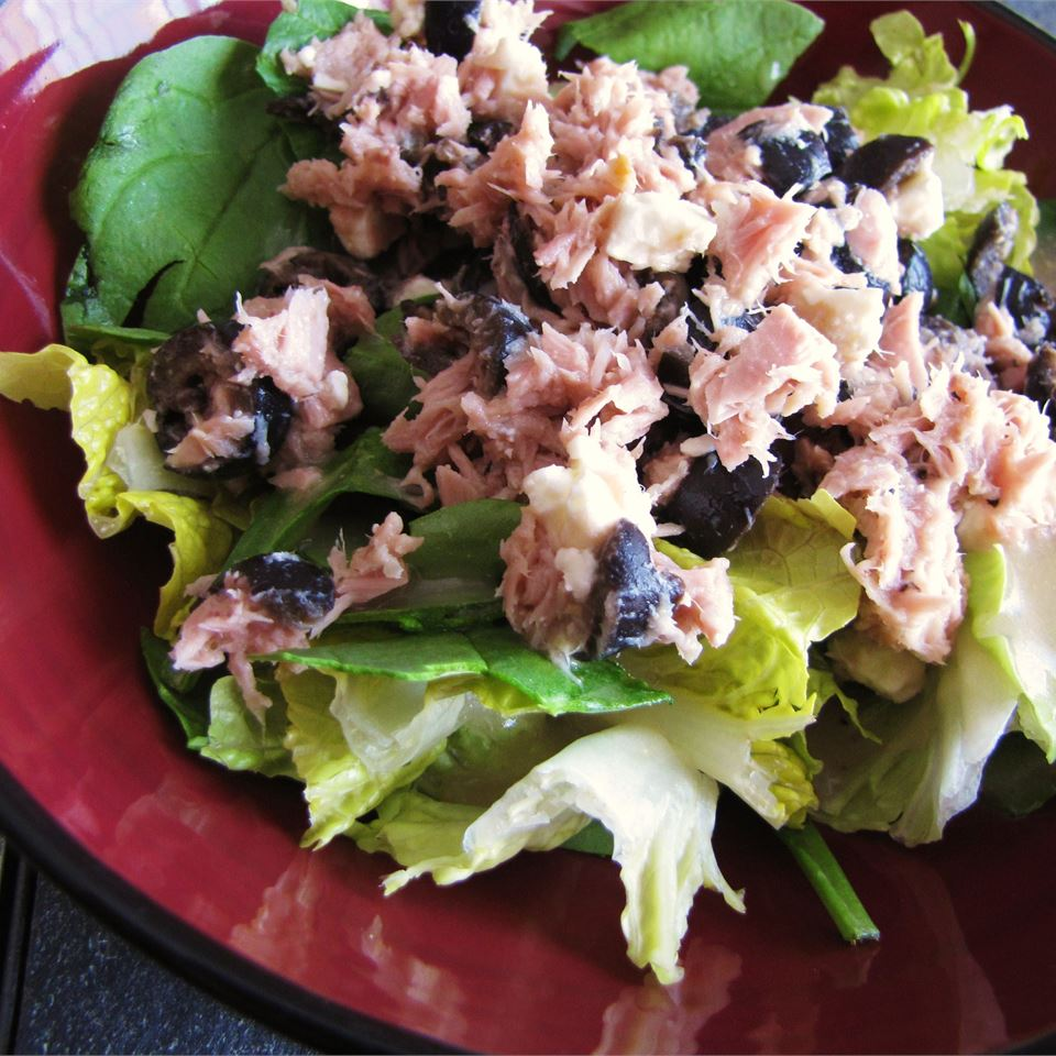 Greek-Style Tuna Salad on a bed of lettuce on a red plate
