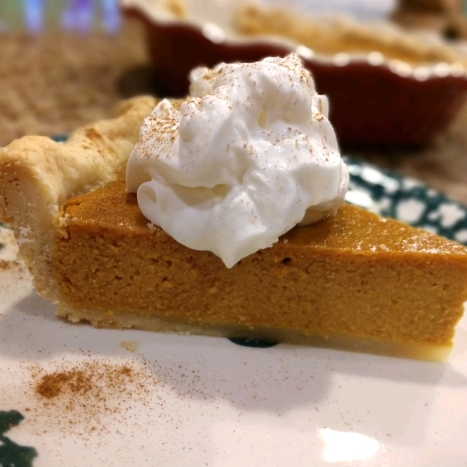 side view of a slice of pumpkin pie with whipped cream on a white plate
