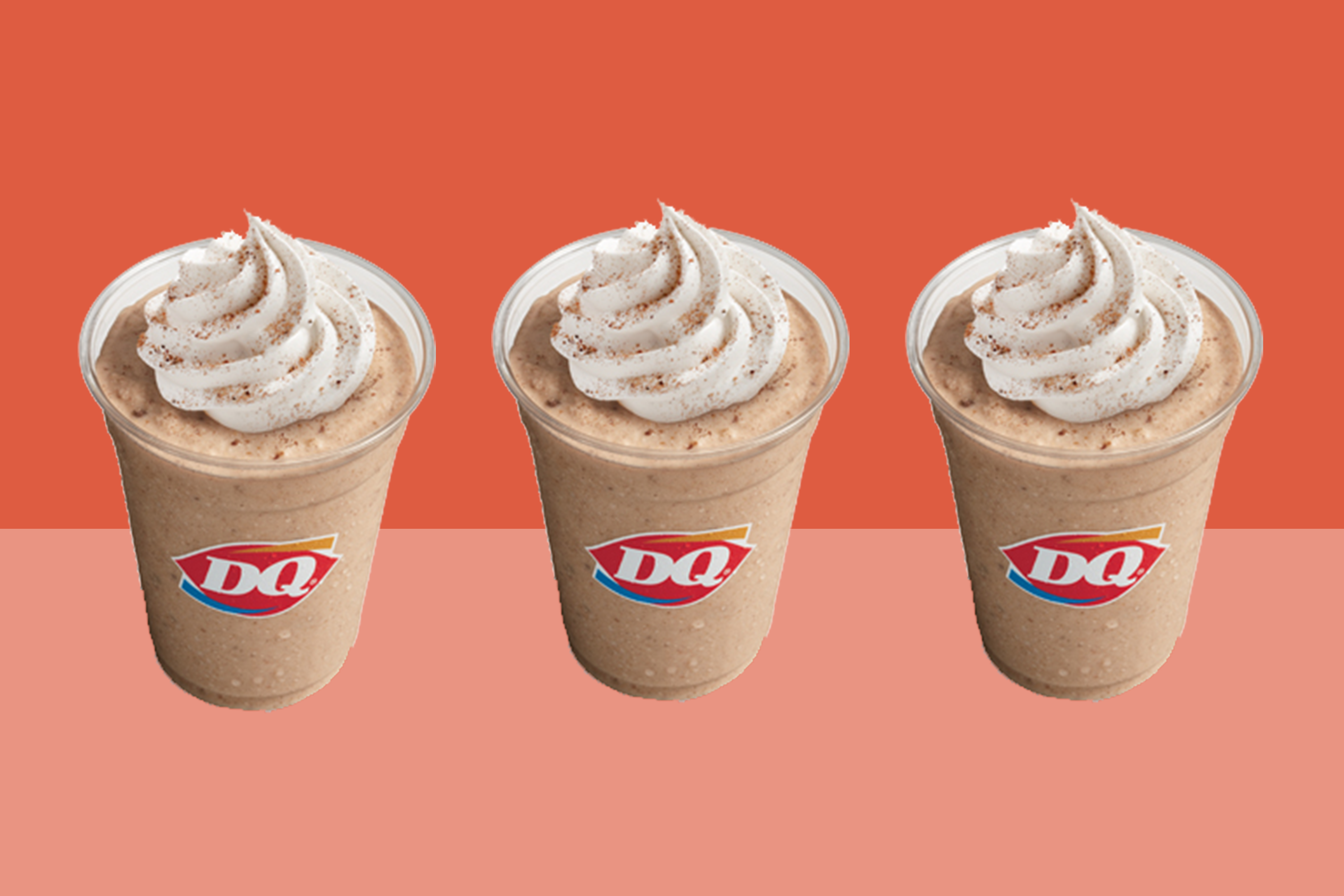 three cups of DQ Pumpkin Cookie Butter Shake on an orange background