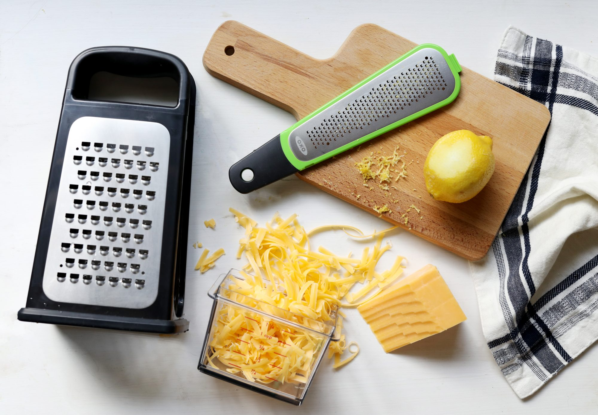 OXO Box Grater with grated cheddar and OXO grater with lemon zest on cutting board.
