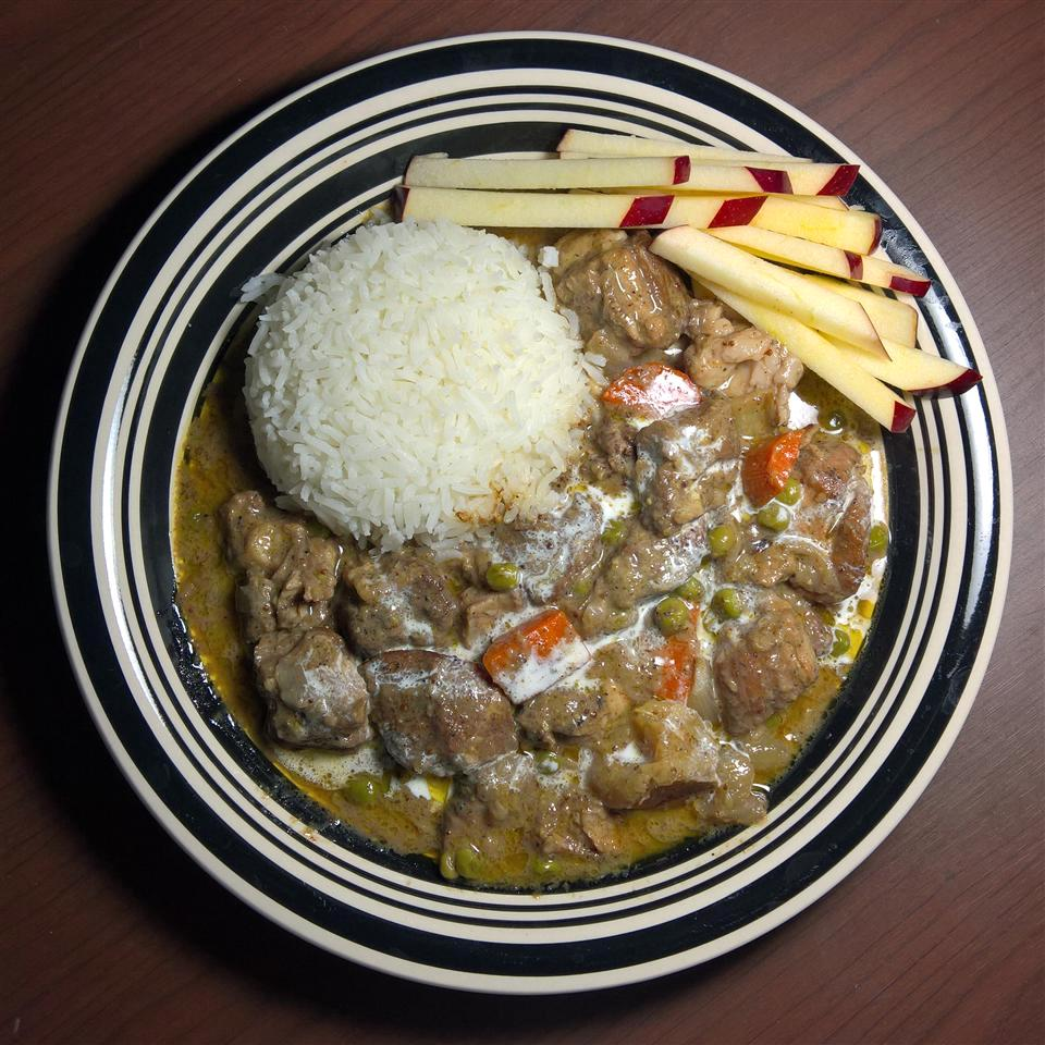 Creamy Pork Stew on a plate with rice and apple slices