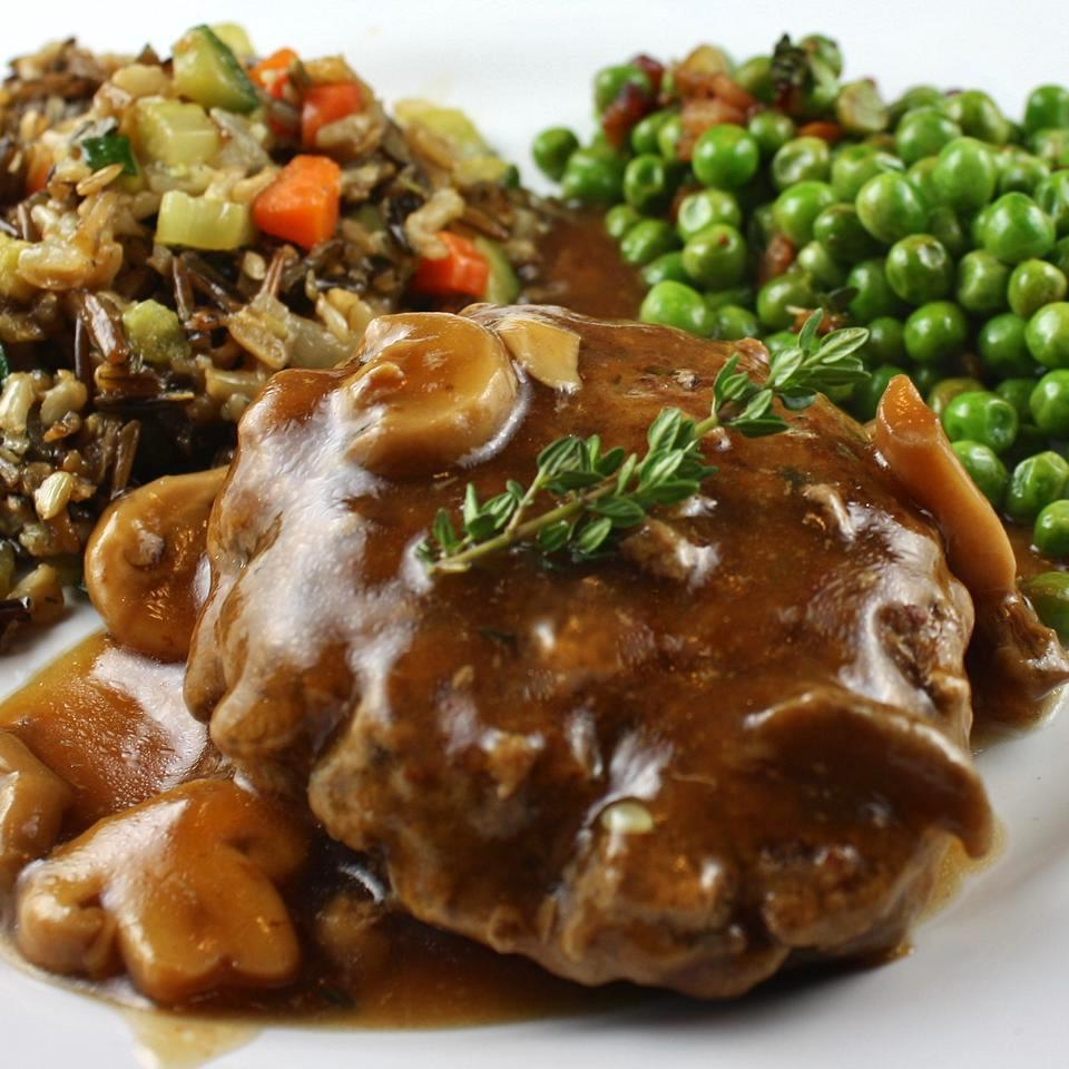 Salisbury Steak with Mushrooms on a white plate with rice and peas