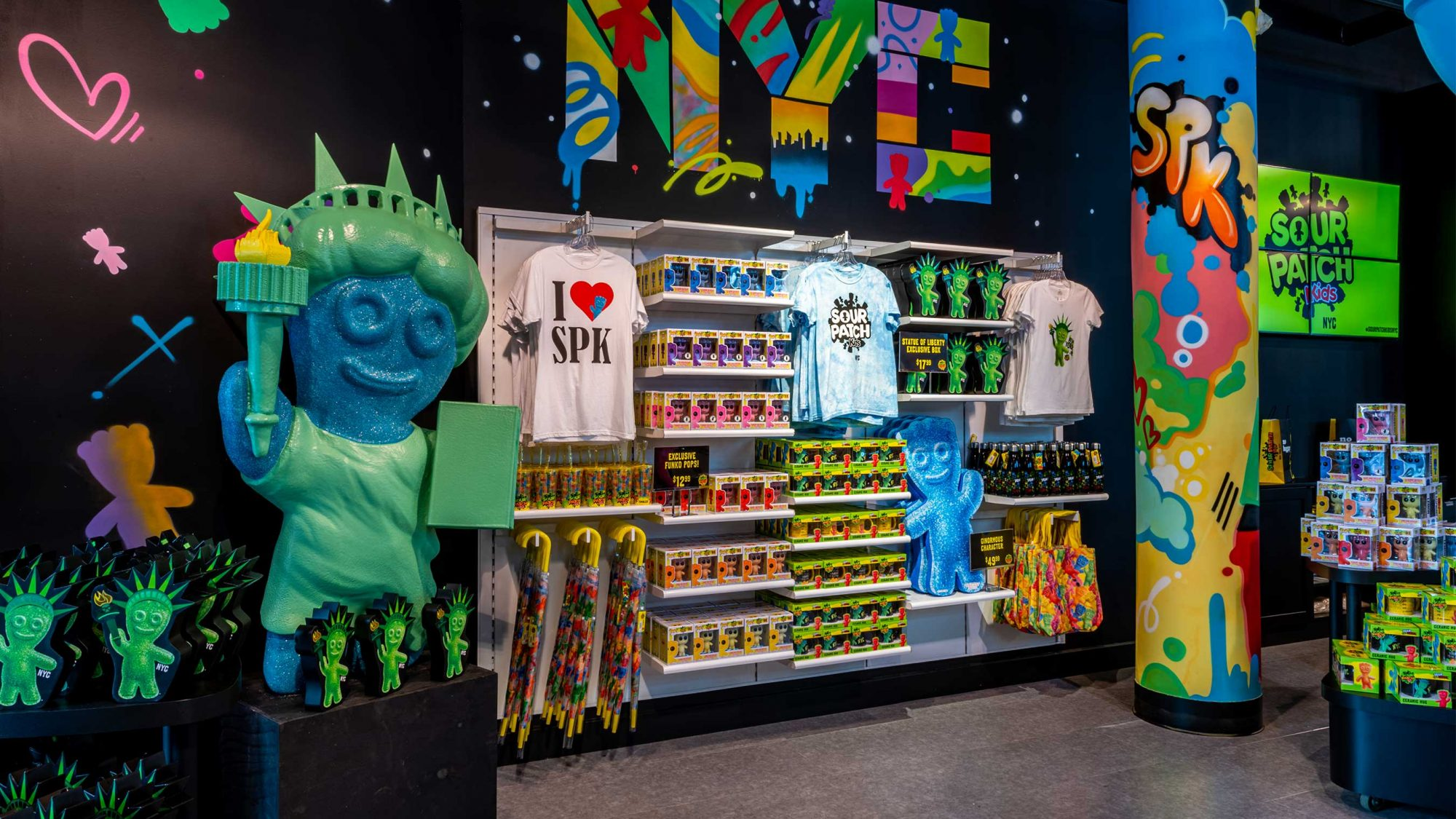 Inside view of sour patch kids store in new york city with hanging shirts and a statue of liberty with sour patch kid