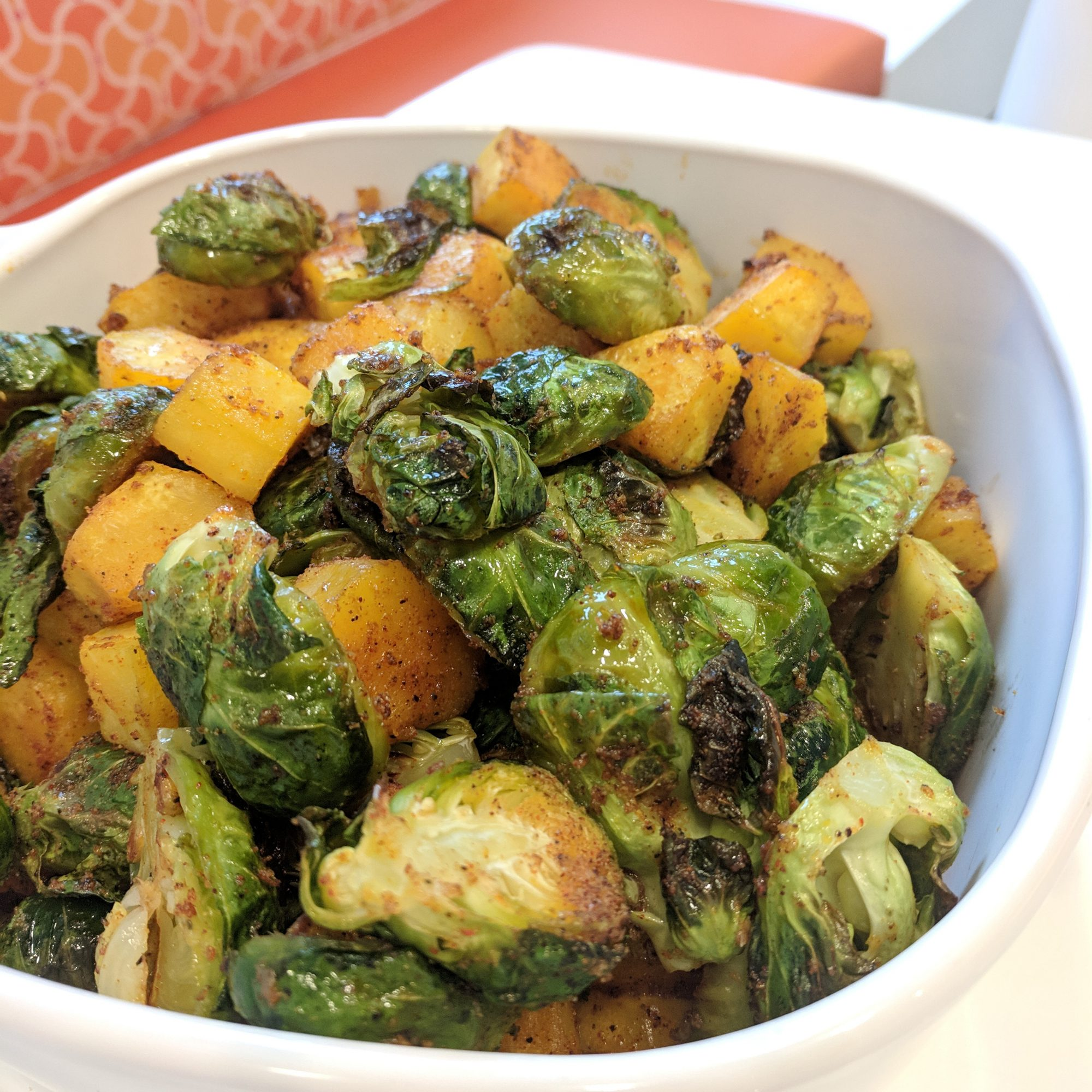Roasted brussels sprouts and squash in a white bowl